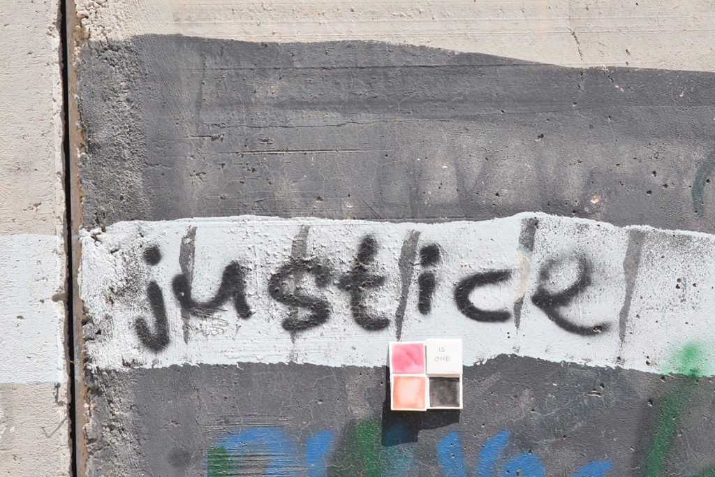 """un graffito con la scritta """"justice"""" sul muro Israele-Palestina con sopra un dono d'arte"""
