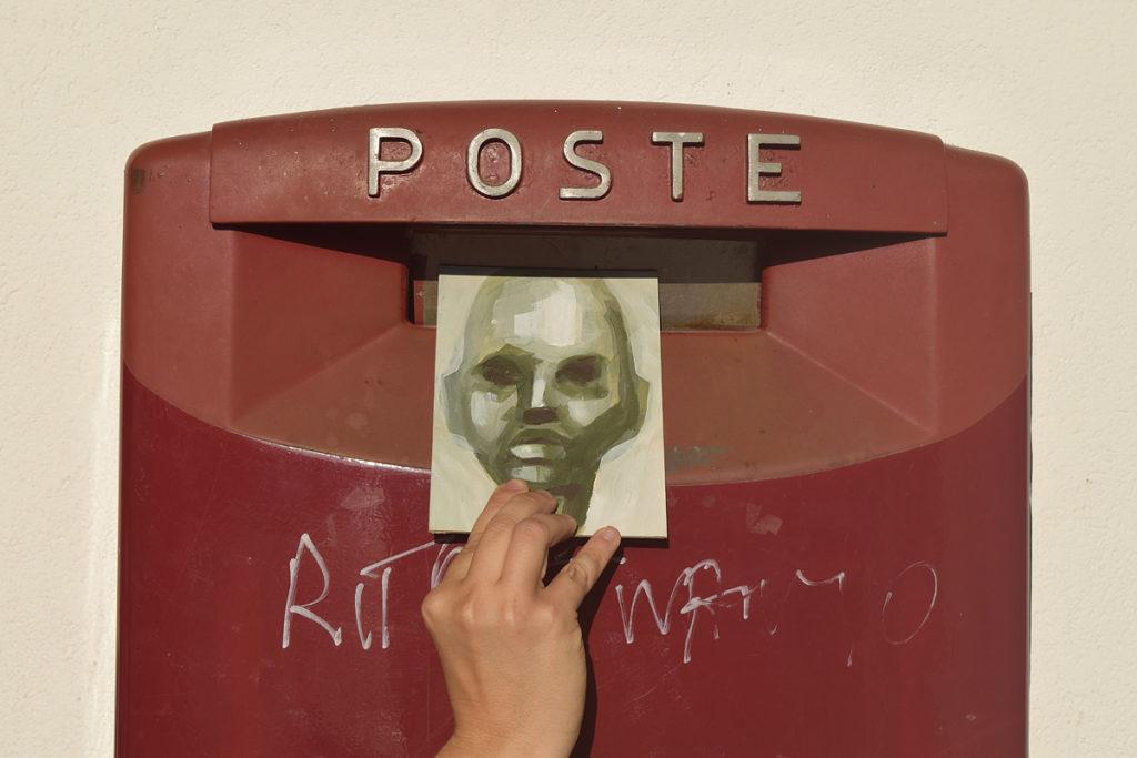 una mano spedisce una cartolina con il ritratto di un uomo dipinto sopra
