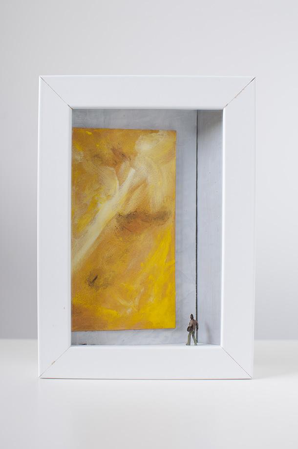un quadro diorama rappresenta un uomo che osserva un enorme quadro tutto giallo.