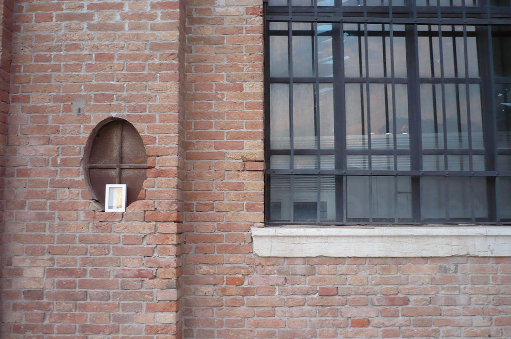 un'opera d'arte abbandonata su una piccola finestra ovale presso l'Arsenale di Venezia