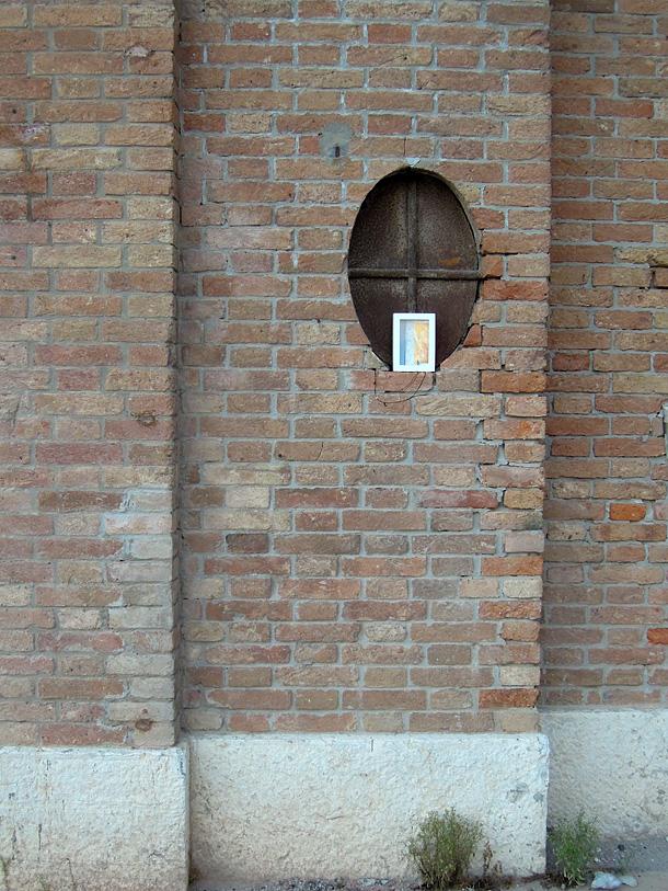 Dono d'arte appoggiato su una piccola finestra ovale dell'arsenale di Venezia