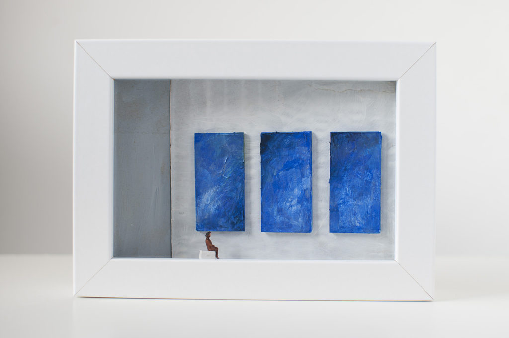 Dono d'arte per la Biennale di Venezia una donna seduta osserva tre quadri blu monocromi