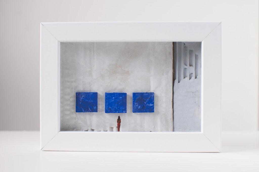 Dono d'arte per la Biennale di Venezia una donna guarda tre quadri blu monocromi
