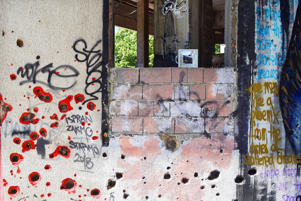 dono d'arte abbandonato su un muro con street art e buchi da sparo