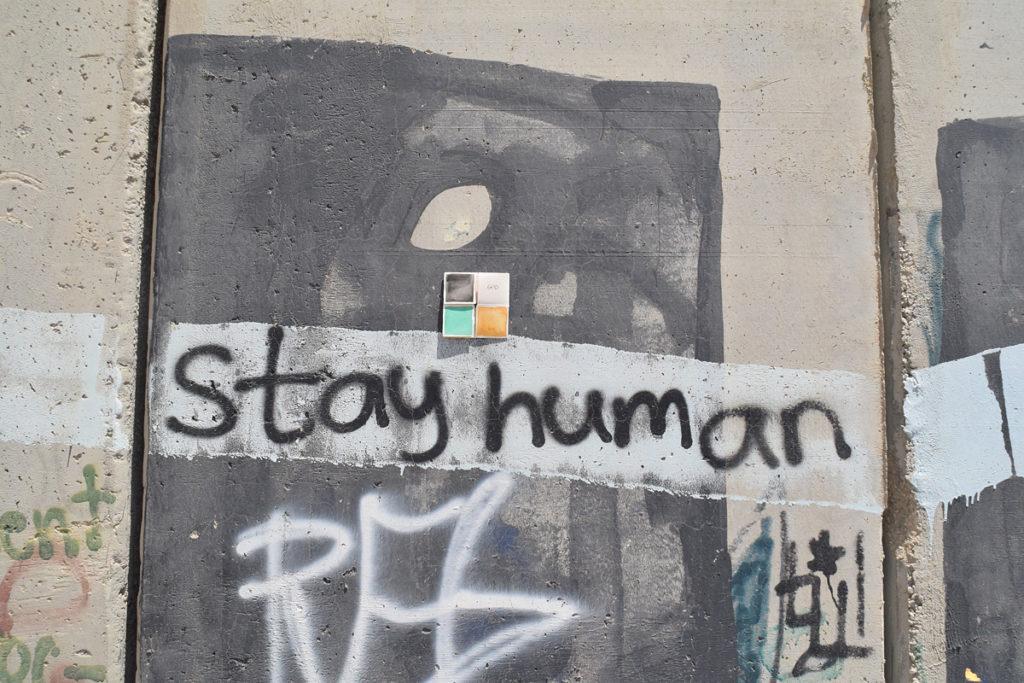 """un graffito sul muro Israele Palestina con la scritta """"stay human"""" con un dono d'arte abbandonato sopra"""