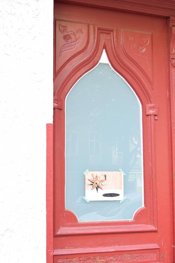 Un dono d'arte viene appeso ad una porta rossa in stile moresco