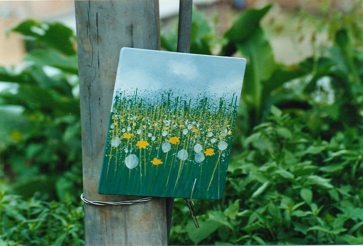 un quadro con i fiori abbandonato su un palo della luce