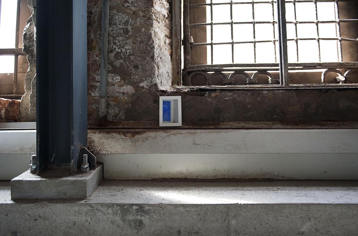 un quadro lasciato sul davanzale di una finestra industriale