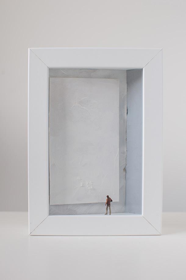 un quadro diorama rappresenta un uomo che osserva un quadro tutto bianco.