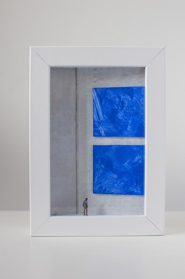 un quadro diorama rappresenta un uomo che osserva due quadri blu.