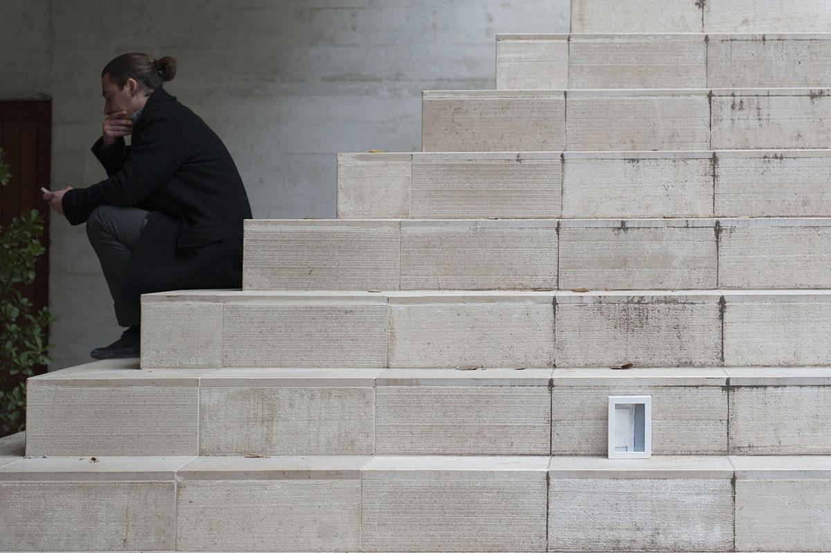un uomo al telefono seduto sulle scale dove è stato abbandonato un quadro