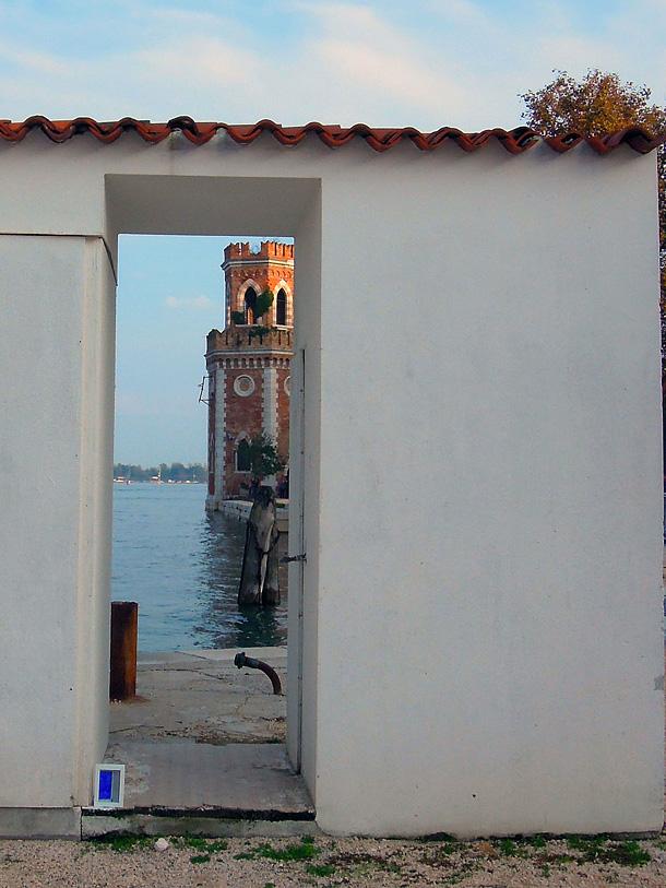 uno scorcio della torre dell'arsenale di Venezia e un dono d'arte abbandonato ai piedi di una casetta