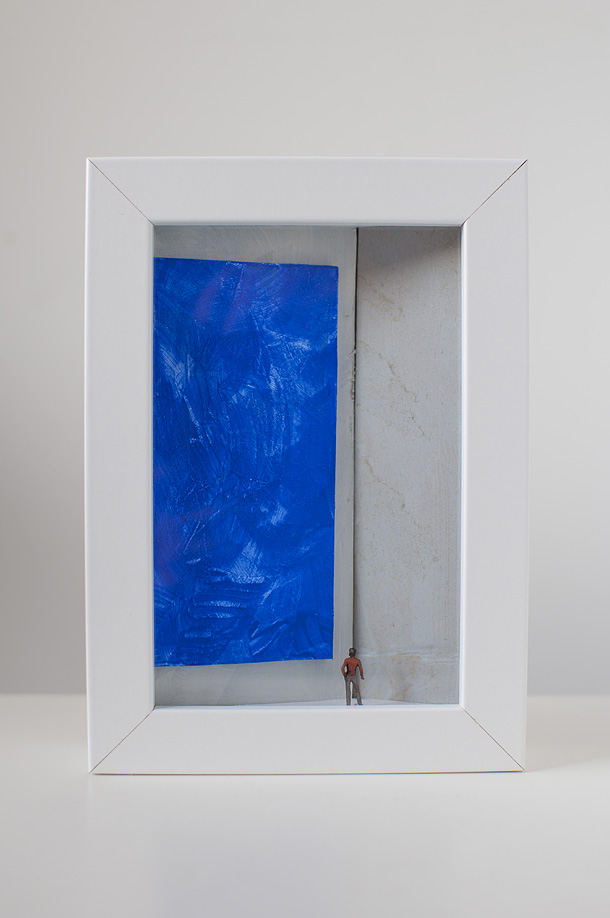 una donna in una galleria d'arte osserva un quadro blu