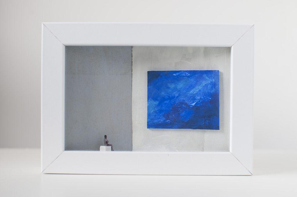 Dono d'arte per la Biennale di Venezia un uomo seduto osserva un quadro blu monocromo