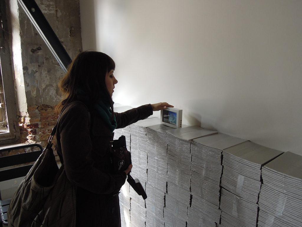 Stefania Bressani lascia un quadro su una pigna di libri